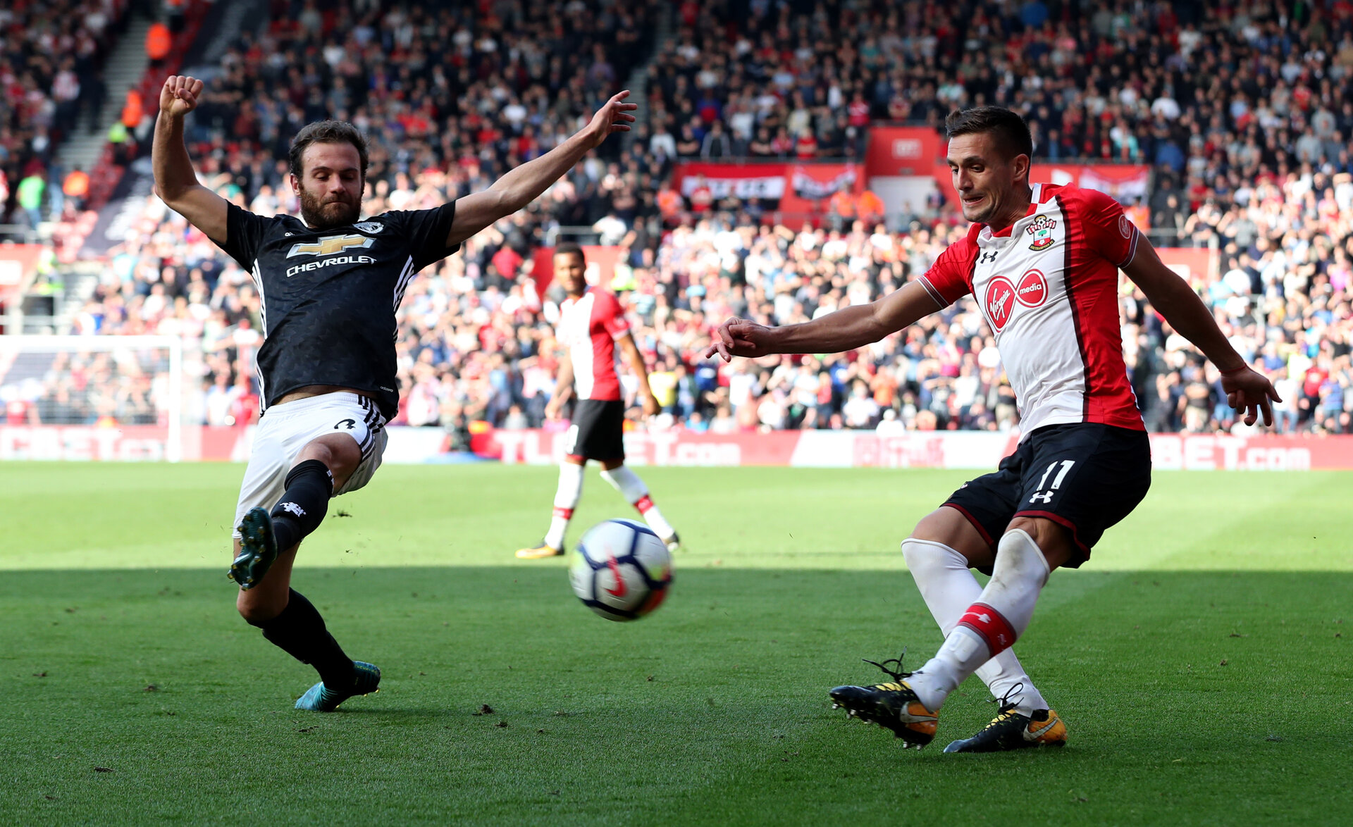 SOUTHAMPTON, ENGLAND - SEPTEMBER 23: Dusan Tadic of Southampton crosses while under pressure from Juan Mata of Manchester United during the Premier League match between Southampton and Manchester United at St Mary's Stadium on September 23, 2017 in Southampton, England. (Photo by Matt Watson/Southampton FC via Getty Images)
