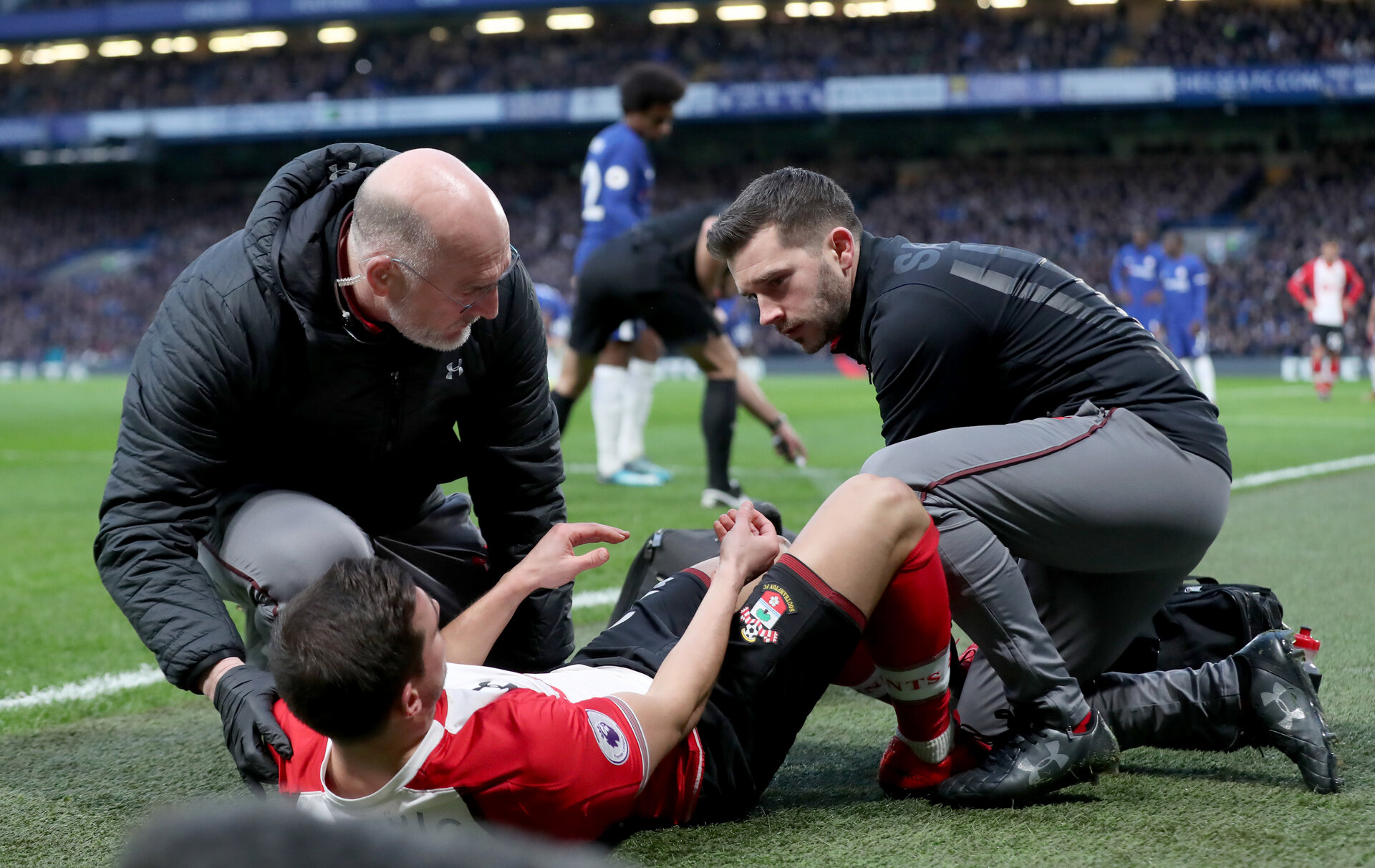 LONDON, ENGLAND - DECEMBER 16: Cedric receives treatment from Doctor Steve Baynes(L) and Kevin Mulholland during the Premier League match between Chelsea and Southampton at Stamford Bridge on December 16, 2017 in London, England. (Photo by Matt Watson/Southampton FC via Getty Images)