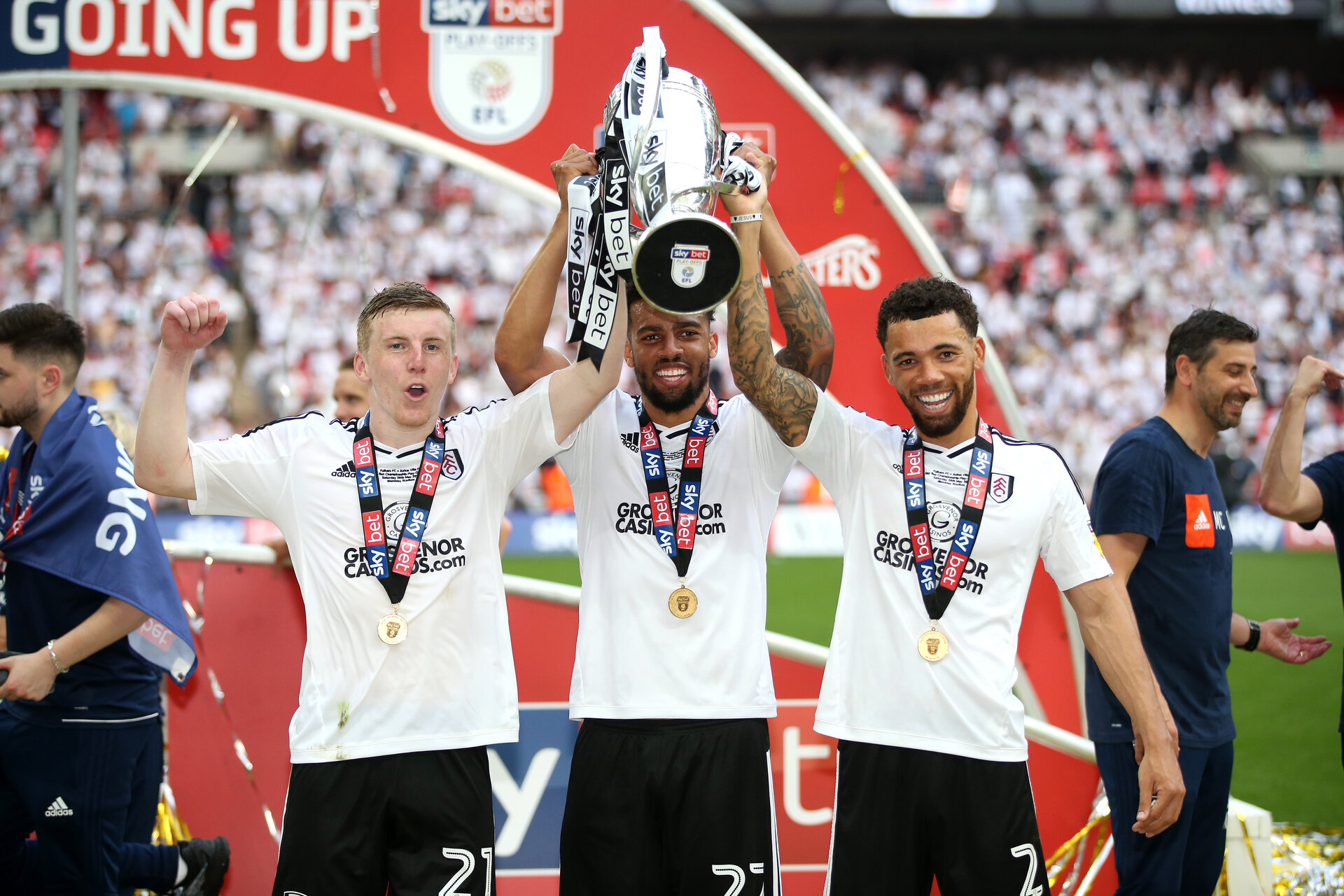 LONDON, ENGLAND - MAY 26:  Matt Targett of Fulham, Cyrus Christie of Fulham, and Ryan Fredericks of Fulham celebrate with the trophy following their sides victory in the Sky Bet Championship Play Off Final between Aston Villa and  Fulham at Wembley Stadium on May 26, 2018 in London, England.  (Photo by Alex Morton/Getty Images)