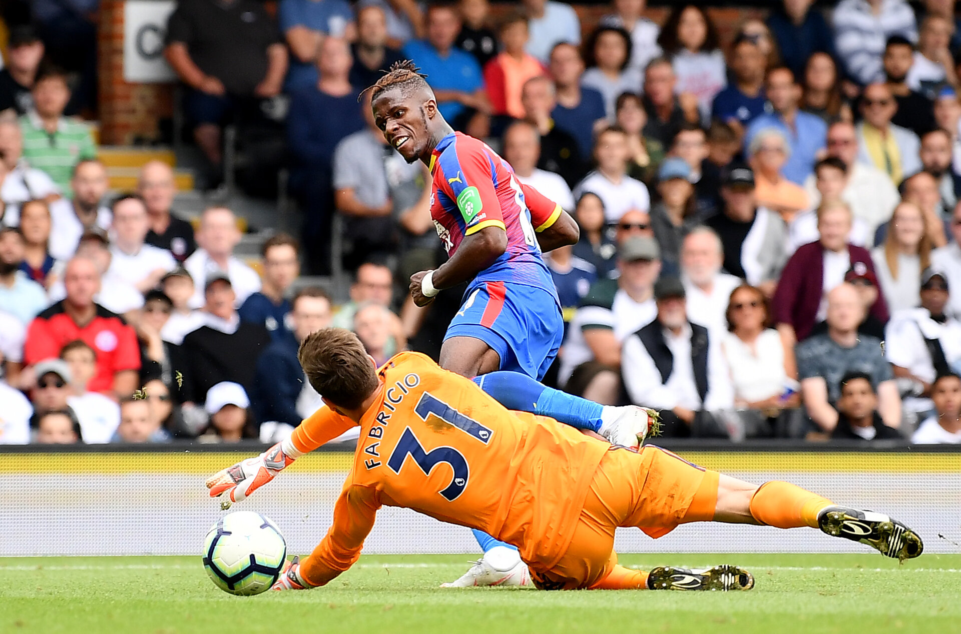 LONDON, ENGLAND - AUGUST 11:  Wilfried Zaha of Crystal Palace scores his team's second goal past Fabricio Agosto Ramirez of Fulham during the Premier League match between Fulham FC and Crystal Palace at Craven Cottage on August 11, 2018 in London, United Kingdom.  (Photo by Justin Setterfield/Getty Images)