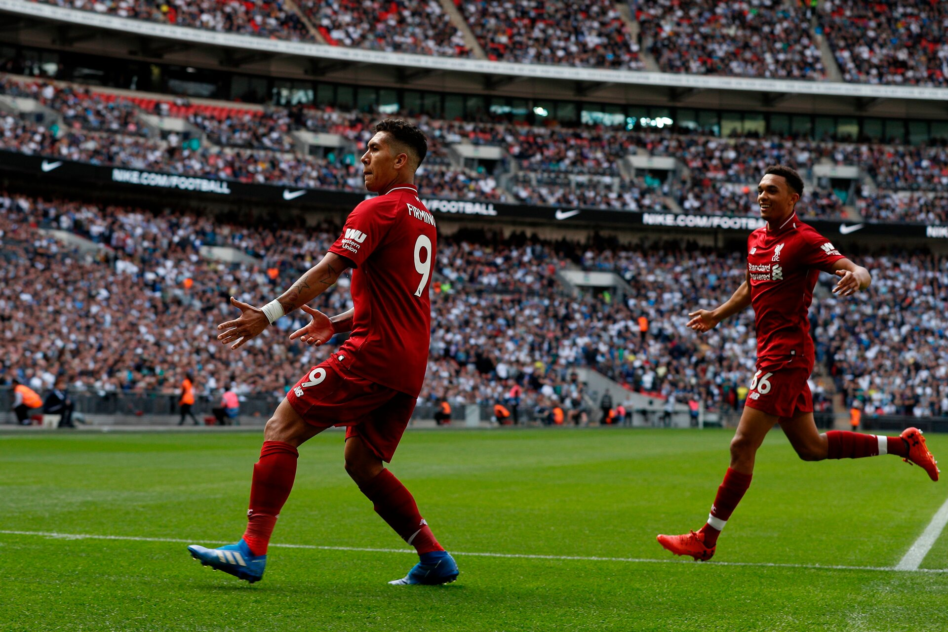 Liverpool's Brazilian midfielder Roberto Firmino (L) celebrates after scoring their second goal with Liverpool's English defender Trent Alexander-Arnold during the English Premier League football match between Tottenham Hotspur and Liverpool at Wembley Stadium in London, on September 15, 2018. (Photo by Adrian DENNIS / AFP) / RESTRICTED TO EDITORIAL USE. No use with unauthorized audio, video, data, fixture lists, club/league logos or 'live' services. Online in-match use limited to 120 images. An additional 40 images may be used in extra time. No video emulation. Social media in-match use limited to 120 images. An additional 40 images may be used in extra time. No use in betting publications, games or single club/league/player publications. /         (Photo credit should read ADRIAN DENNIS/AFP/Getty Images)