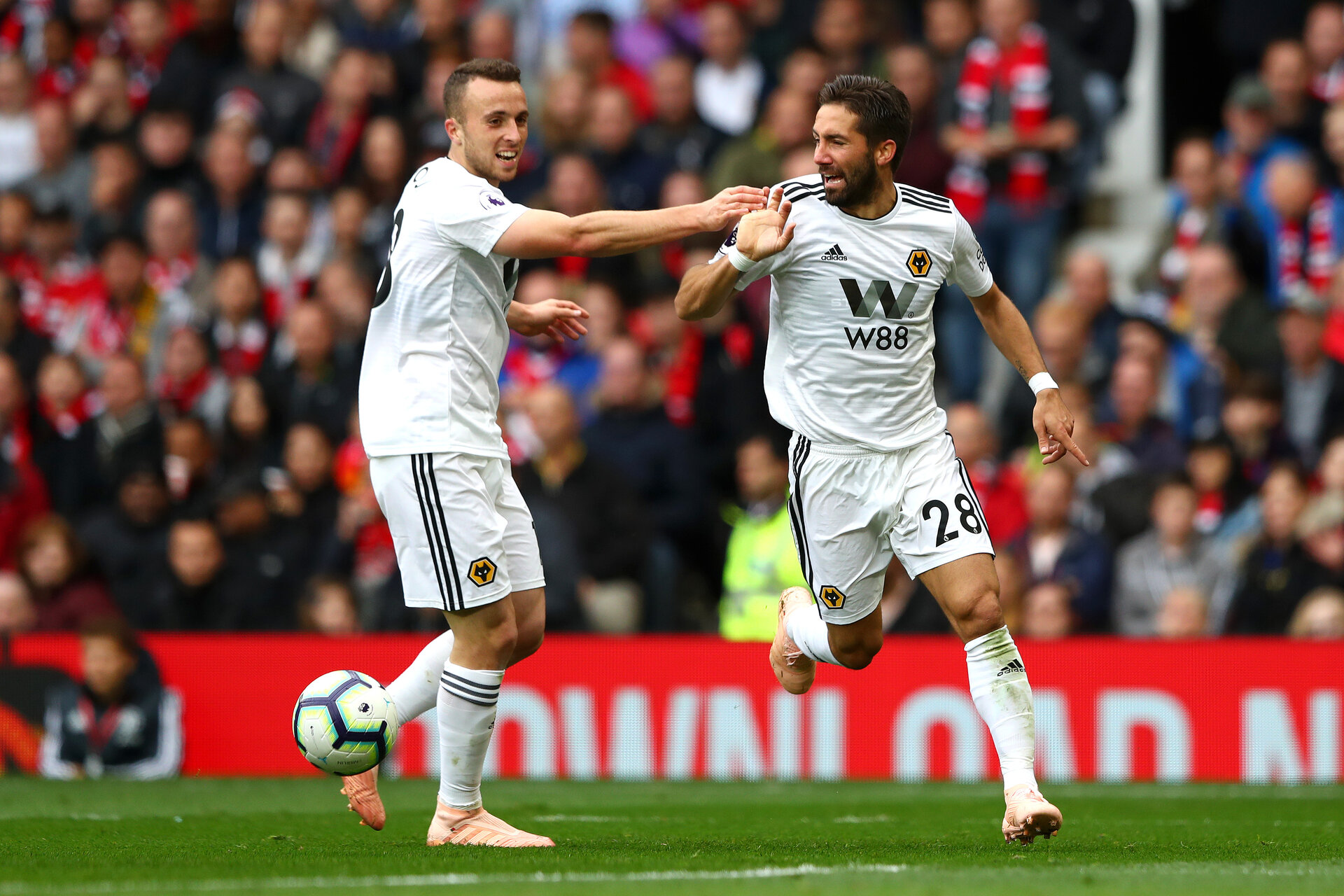 MANCHESTER, ENGLAND - SEPTEMBER 22:  Joao Moutinho of Wolverhampton Wanderers celebrates with teammate Diogo Jota after scoring his team's first goal during the Premier League match between Manchester United and Wolverhampton Wanderers at Old Trafford on September 22, 2018 in Manchester, United Kingdom.  (Photo by Matthew Lewis/Getty Images)