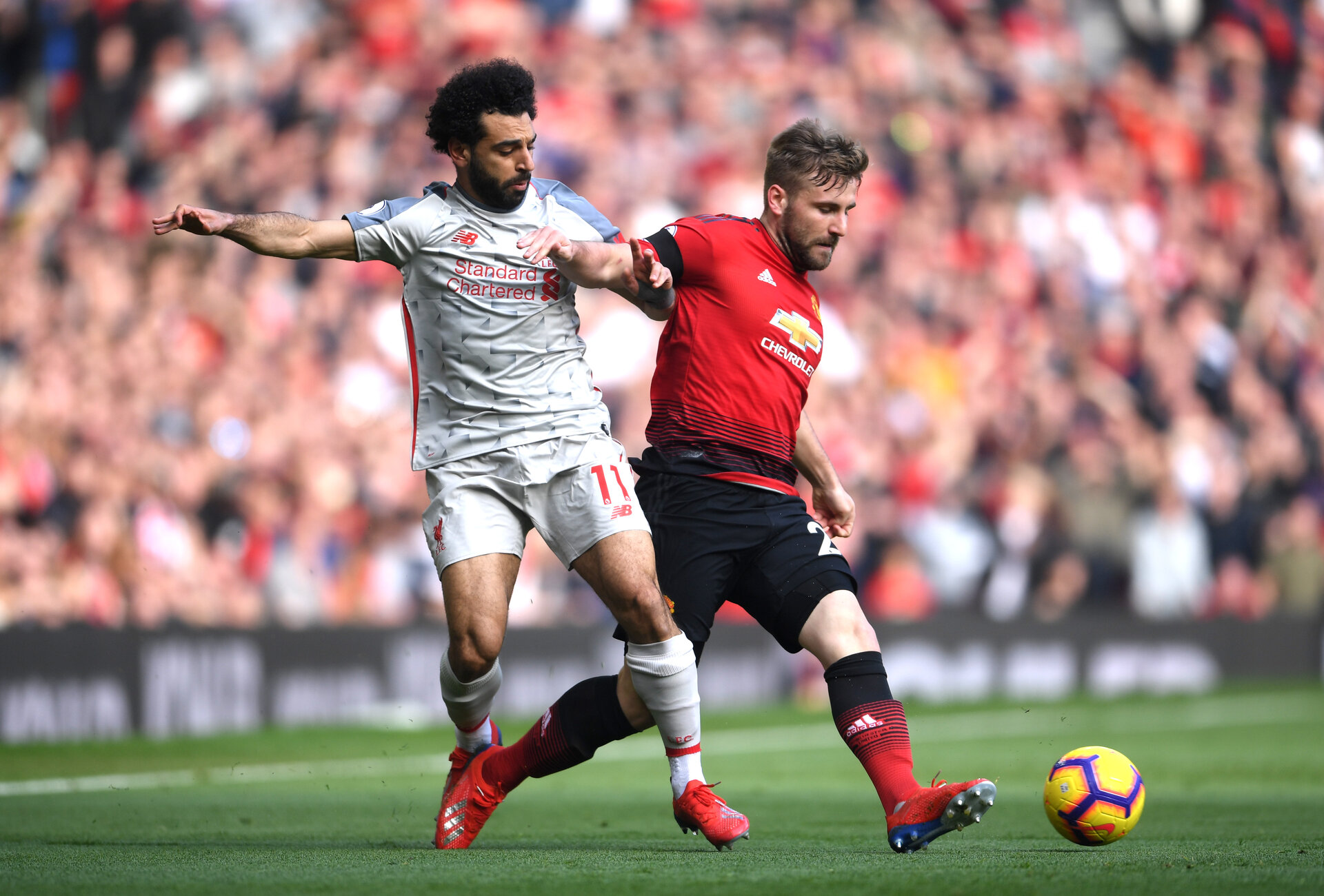 MANCHESTER, ENGLAND - FEBRUARY 24:  Luke Shaw of Manchester United battles for possession with Mohamed Salah of Liverpool during the Premier League match between Manchester United and Liverpool FC at Old Trafford on February 24, 2019 in Manchester, United Kingdom.  (Photo by Laurence Griffiths/Getty Images)