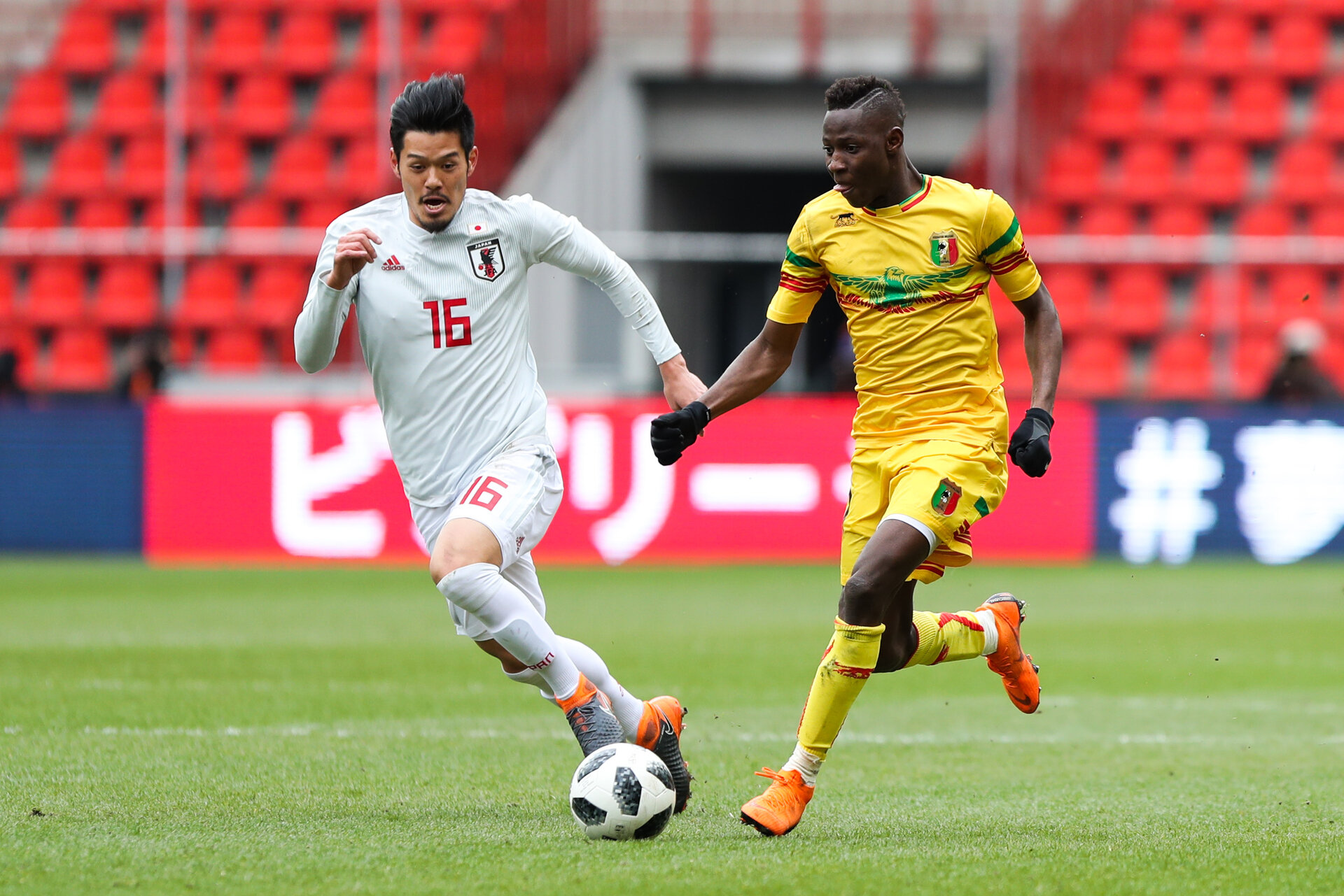Hotaru Yamaguchi of Japan and Moussa Djenepo of Mali during the International friendly match between Japan and Mali on March 23, 2018 in Liege, Belgium. (Photo by Johnny Fidelin/Icon Sport via Getty Images)