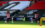 SOUTHAMPTON, ENGLAND - JUNE 25: Nathan Redmond(L) and Michael Obafemi of Southampton take a knee as part of the Black Lives Matter movement during the Premier League match between Southampton FC and Arsenal FC at St Mary's Stadium on June 25, 2020 in Southampton, United Kingdom. (Photo by Matt Watson/Southampton FC via Getty Images)