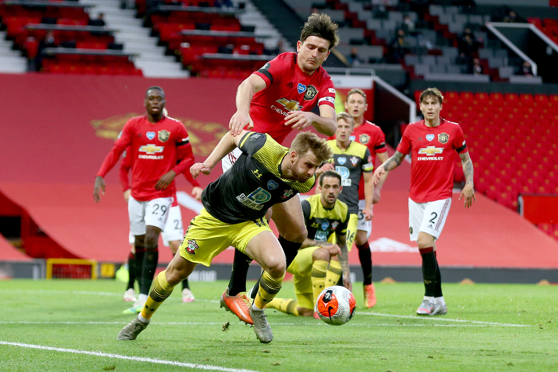 MANCHESTER, ENGLAND - JULY 13: Stuart Armstrong (L) and Harry Maguire (R) during the Premier League match between Manchester United and Southampton FC at Old Trafford on July 13, 2020 in Manchester, United Kingdom. Football Stadiums around Europe remain empty due to the Coronavirus Pandemic as Government social distancing laws prohibit fans inside venues resulting in all fixtures being played behind closed doors. (Photo by Matt Watson/Southampton FC via Getty Images)