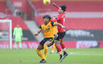SOUTHAMPTON, ENGLAND - FEBRUARY 14: Adama Traore (L) of Wolves and Takumi Minamino (R) of Southampton during the Premier League match between Southampton and Wolverhampton Wanderers at St Mary's Stadium on February 14, 2021 in Southampton, England. Sporting stadiums around the UK remain under strict restrictions due to the Coronavirus Pandemic as Government social distancing laws prohibit fans inside venues resulting in games being played behind closed doors. (Photo by Matt Watson/Southampton FC via Getty Images)