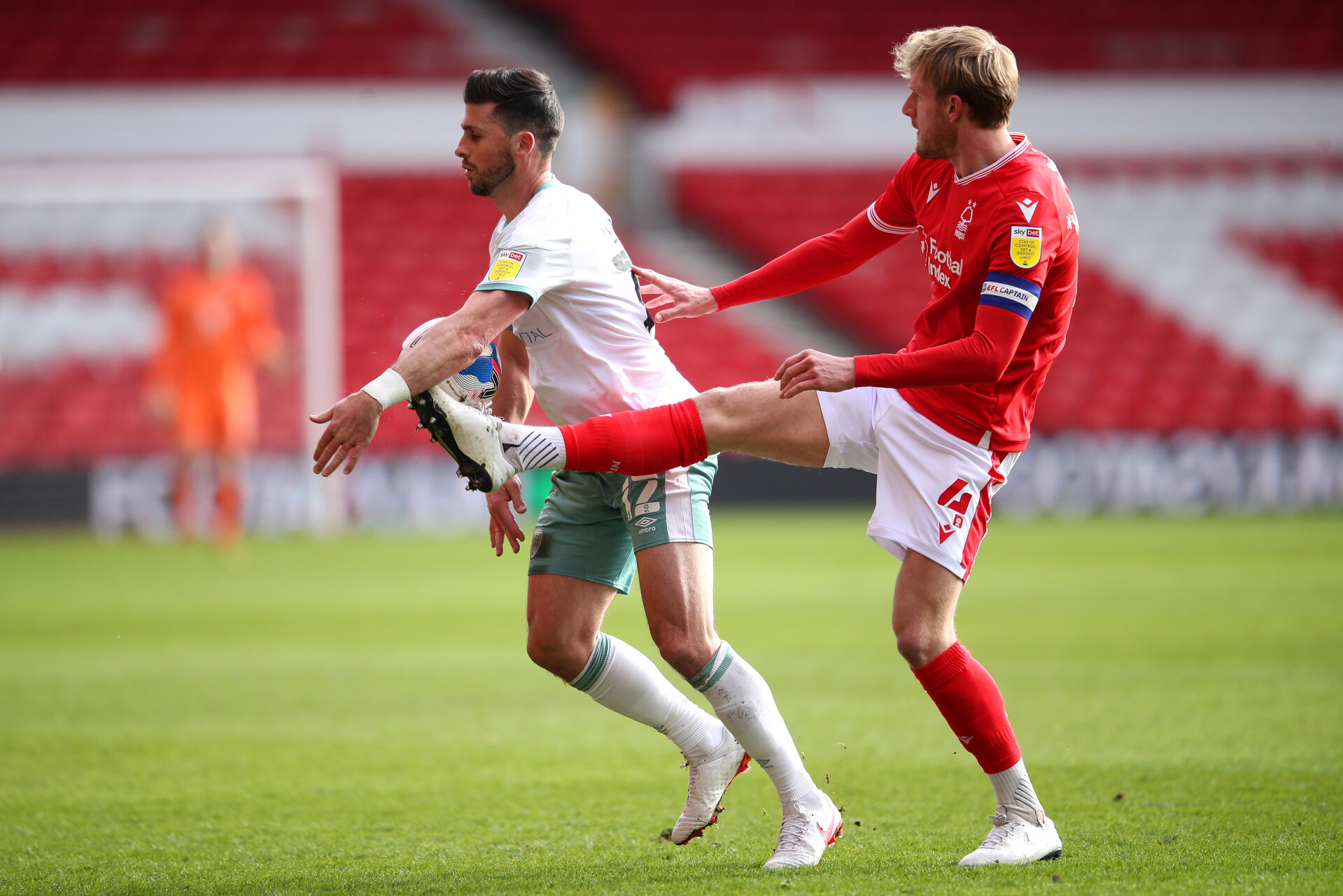 NOTTINGHAM, ENGLAND - FEBRUARY 13: Shane Long of AFC Bournemouth is challenged by Joe Worrall of Nottingham Forest  during the Sky Bet Championship match between Nottingham Forest and AFC Bournemouth at City Ground on February 13, 2021 in Nottingham, England. Sporting stadiums around the UK remain under strict restrictions due to the Coronavirus Pandemic as Government social distancing laws prohibit fans inside venues resulting in games being played behind closed doors. (Photo by Alex Pantling/Getty Images)