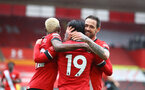 SOUTHAMPTON, ENGLAND - FEBRUARY 20: Moussa Djenepo(L) and Danny Ings (R) congratulate Takumi Minamino (19) on his goal  during the Premier League match between Southampton and Chelsea at St Mary's Stadium on February 20, 2021 in Southampton, England. Sporting stadiums around the UK remain under strict restrictions due to the Coronavirus Pandemic as Government social distancing laws prohibit fans inside venues resulting in games being played behind closed doors. (Photo by Matt Watson/Southampton FC via Getty Images)