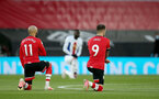 SOUTHAMPTON, ENGLAND - MAY 11: Nathan Redmond(L) and Danny Ings(R) of Southampton take the knee in support of the Black Lives Matter movement during the Premier League match between Southampton and Crystal Palace at St Mary's Stadium on May 11, 2021 in Southampton, England. Sporting stadiums around the UK remain under strict restrictions due to the Coronavirus Pandemic as Government social distancing laws prohibit fans inside venues resulting in games being played behind closed doors.  (Photo by Matt Watson/Southampton FC via Getty Images)