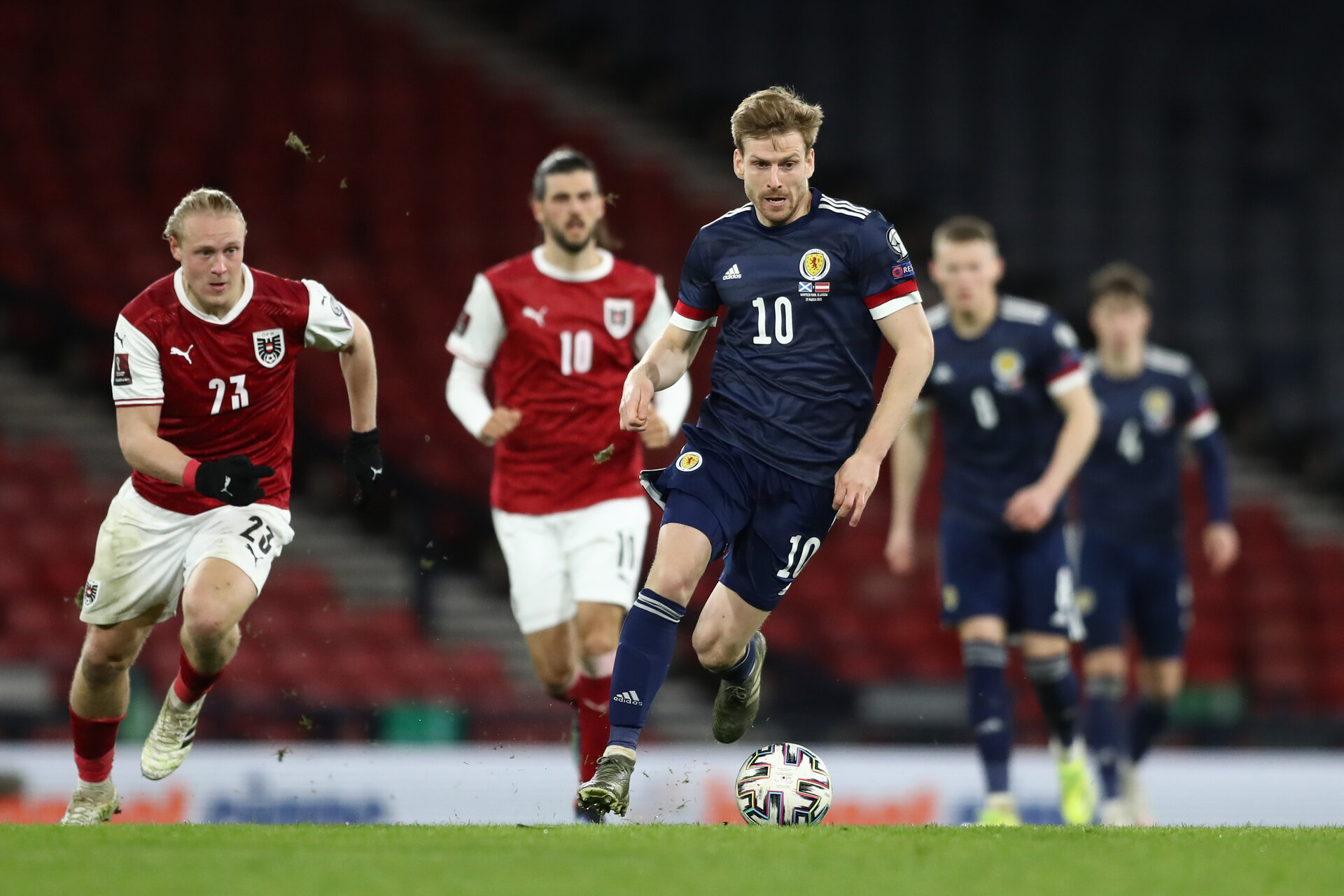 GLASGOW, SCOTLAND - MARCH 25: Stuart Armstrong of Scotland runs with the ball whilst under pressure from Xaver Schlager of Austria during the FIFA World Cup 2022 Qatar qualifying match between Scotland and Austria on March 25, 2021 in Glasgow, Scotland. Sporting stadiums around the UK remain under strict restrictions due to the Coronavirus Pandemic as Government social distancing laws prohibit fans inside venues resulting in games being played behind closed doors. (Photo by Jan Kruger - UEFA/UEFA via Getty Images)