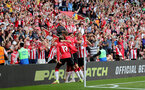 SOUTHAMPTON, ENGLAND - AUGUST 22: Che Adams of Southampton celebrates with team mates after opening the scoring during the Premier League match between Southampton  and  Manchester United at St Mary's Stadium on August 22, 2021 in Southampton, England. (Photo by Isabelle Field/Southampton FC via Getty Images)