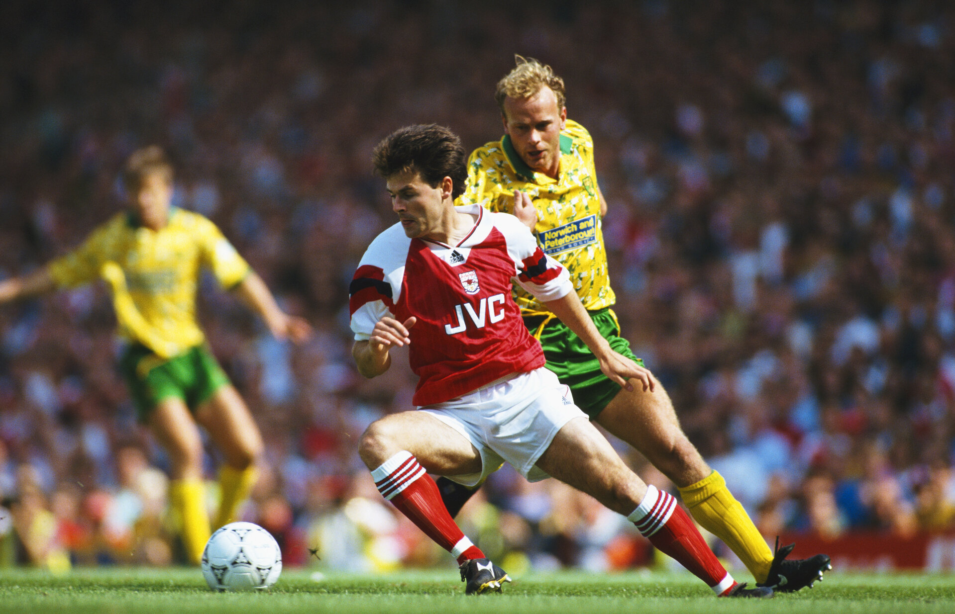 LONDON, UNITED KINGDOM - AUGUST 15: Arsenal wing Anders Limpar holds off the challenge of Jeremy Goss during a FA Premier League match between Arsenal and Norwich City at Higbury on August 15, 1992 in London, England. (Photo by Ben Radford/Allsport/Getty Images)